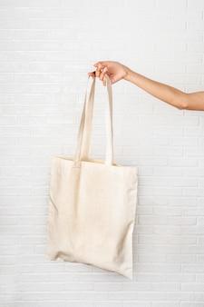 Weibliche hand, die eco tasche auf weißem hintergrund hält