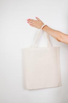 Weibliche hand, die ecobag mocap aus wiederverwendbarem baumwoll-ecobag auf weißem isoliertem hintergrundkonzept von ...