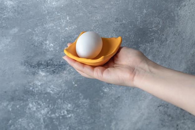 Weibliche hand, die ei in gelber schüssel hält.
