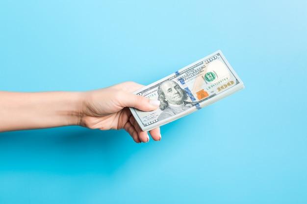 Weibliche hand, die ein bündel dollarscheine auf blau gibt. macht und reichtum
