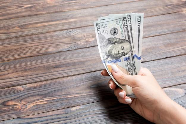 Weibliche hand, die ein bündel von einhundert dollar-banknoten auf hölzernem hintergrund hält. gehalts- und lohnkonzept mit kopierraum