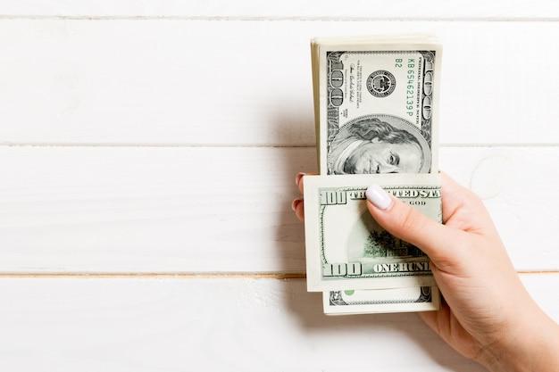 Weibliche hand, die ein bündel von einhundert dollar hält