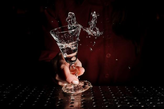 Weibliche hand, die ein cocktailglas füllte mit einem neuen getränk anhält