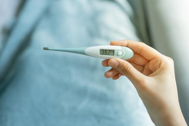 Weibliche hand, die ein digitales thermometer hält