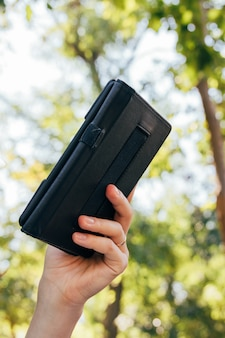 Weibliche hand, die ein ebook in der abdeckung auf dem hintergrund von bäumen hält