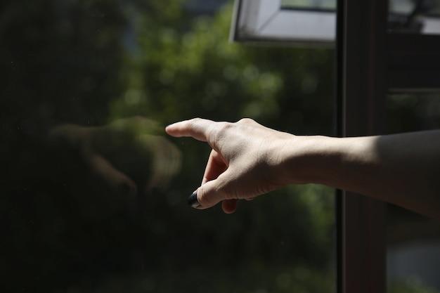 Weibliche hand, die ein fenster berührt und nach außen zeigt
