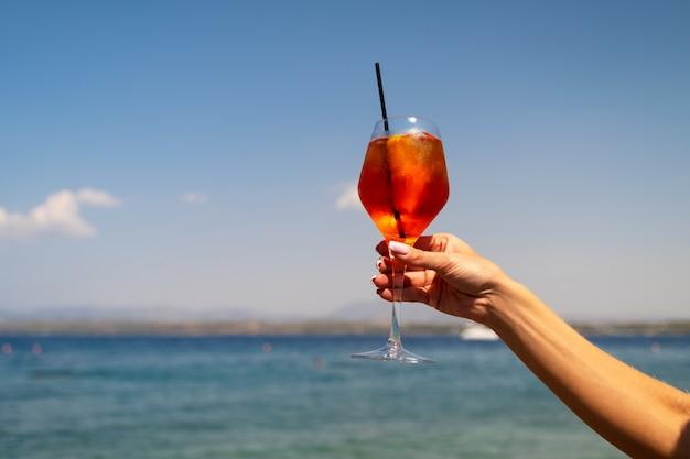 Weibliche hand, die ein glas aperol-spritz-cocktail auf meereshintergrund hält