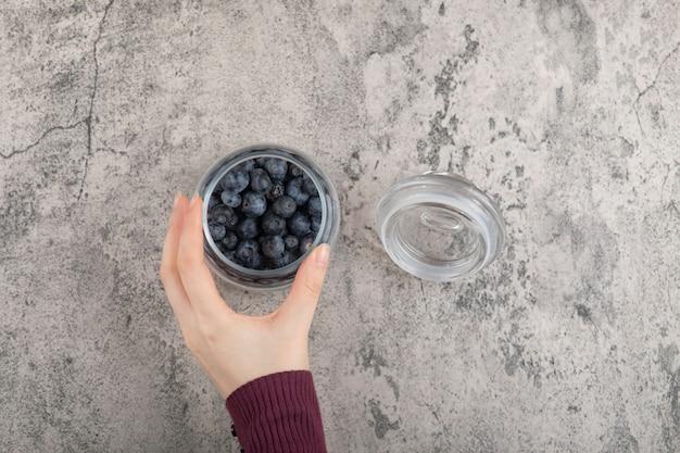 Weibliche hand, die ein glas frische blaubeeren auf marmoroberfläche hält
