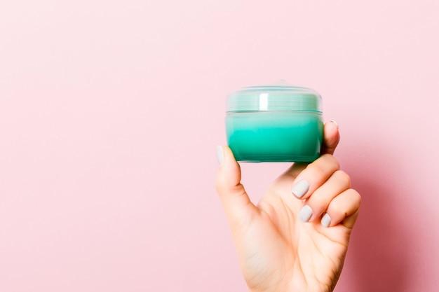Weibliche hand, die ein glas kosmetikprodukt auf rosafarbenem hintergrund mit leerem raum für ihr design hält.