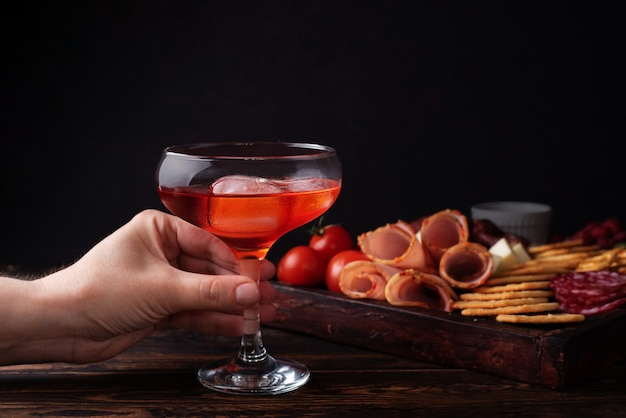 Weibliche hand, die ein glas roten schnaps und wurstwarenbrett hält, alkoholischer cocktail mit einer vorspeise, nahaufnahme.