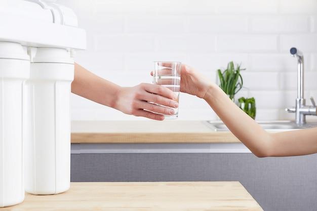 Weibliche hand, die ein glas sauberes wasser gibt
