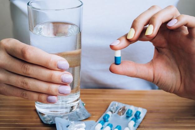 Weibliche hand, die ein glas wasser und pille hält