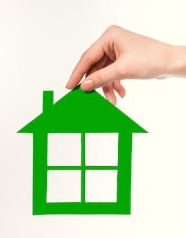 Weibliche hand, die ein grünbuchhaus hält