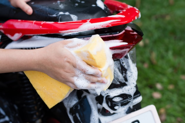 Weibliche hand, die ein motorrad wäscht.