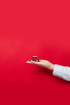 Weibliche hand, die ein rotes modellauto des spielzeugs auf einem roten hintergrund hält. weihnachts- und neujahrsfeiertagshintergrund.