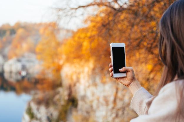 Weibliche hand, die ein telefon, schwarzen bildschirm anhält