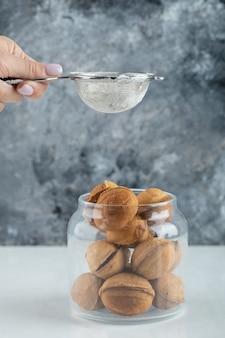 Weibliche hand, die ein zuckerpulver auf walnussförmige kekse streut.