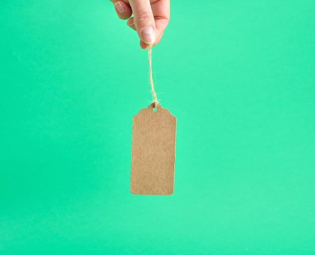 Weibliche hand, die eine braune leere papiermarke auf einem seil anhält