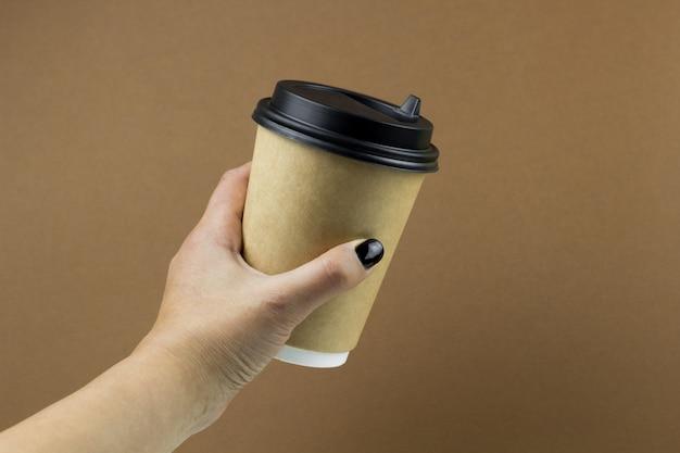 Weibliche hand, die eine ccoffee-papierschale auf braunem hintergrund hält