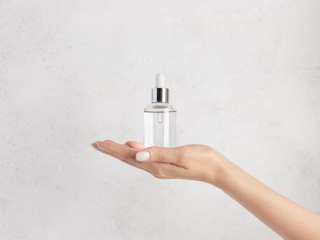 Weibliche hand, die eine glasflasche mit kollagen hält