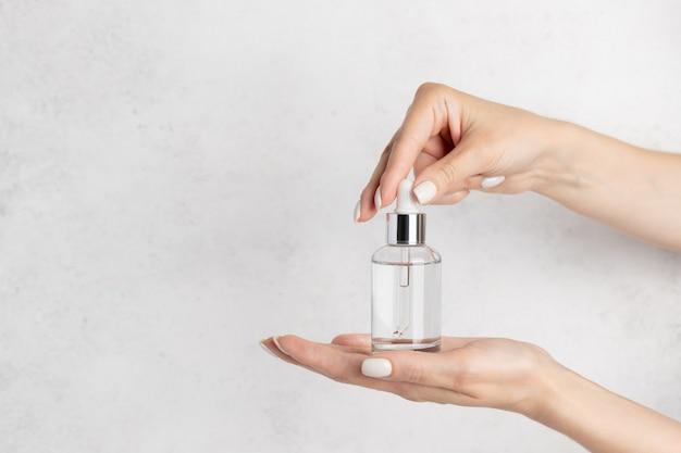 Weibliche hand, die eine glasflasche mit kosmetischem serum öffnet.