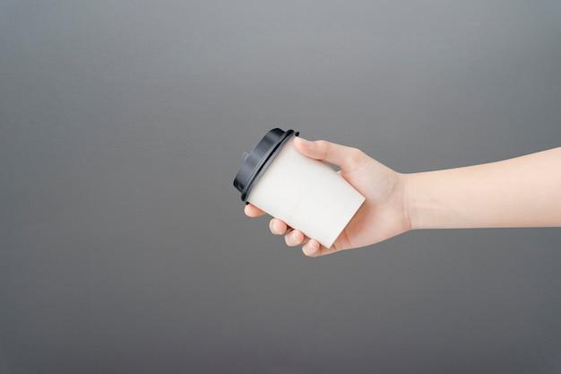 Weibliche hand, die eine kaffeepapiertasse auf grau hält