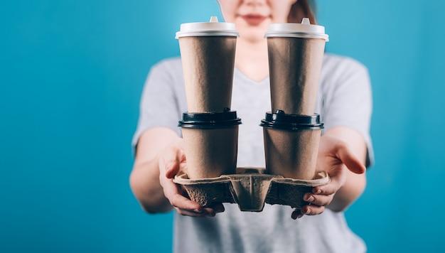 Weibliche hand, die eine kaffeepapiertasse hält