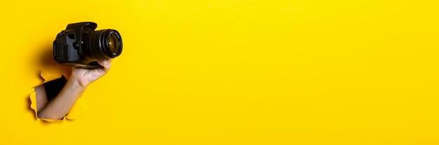 Weibliche hand, die eine kamera auf einem hellen gelben hintergrund hält