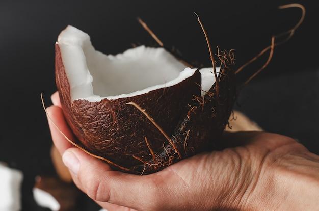 Weibliche hand, die eine kokosnusshälfte auf schwarzem hält
