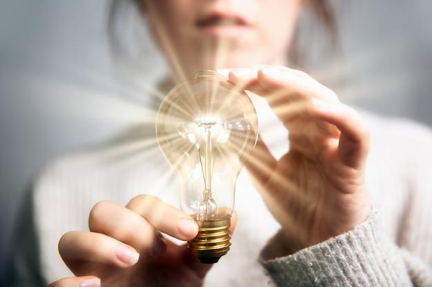 Weibliche hand, die eine leuchtende glühbirne hält, großartige idee, innovation und inspiration, geschäftskonzept zurück...