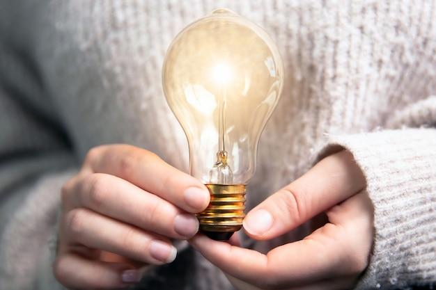 Weibliche hand, die eine leuchtende glühbirne hält