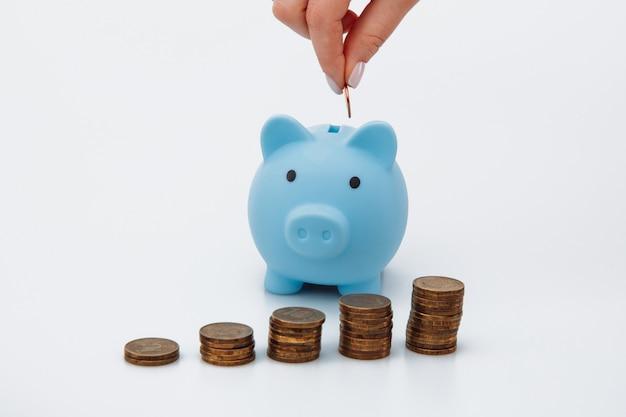 Weibliche hand, die eine münze in ein blaues sparschwein legt. geldsparendes konzept