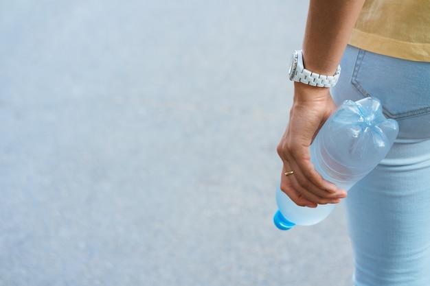 Weibliche hand, die eine plastikwasserflasche hält