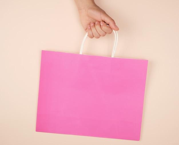 Weibliche hand, die eine rosa papiereinkaufstasche hält