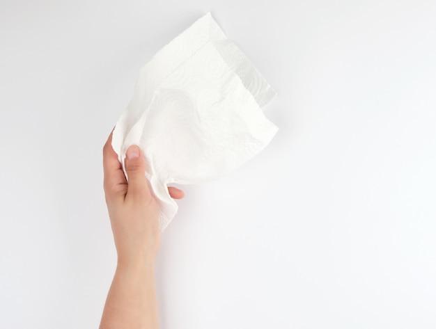 Weibliche hand, die eine saubere weißbuchserviette hält
