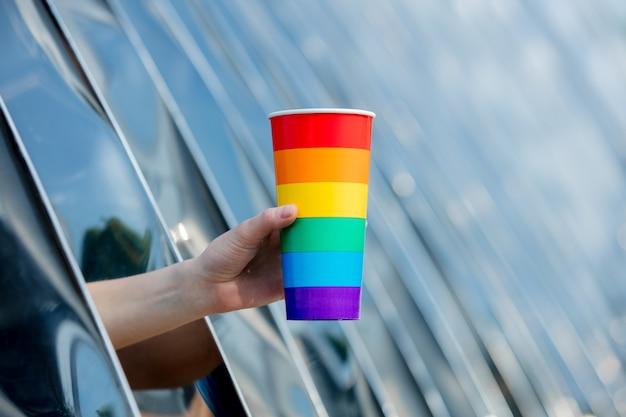 Weibliche hand, die eine tasse in der farbe der lgbt-flagge auf dem hintergrund der metallkonstruktion hält