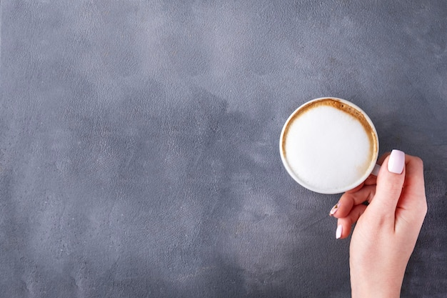 Weibliche hand, die eine tasse kaffee hält. draufsicht, kopierraum