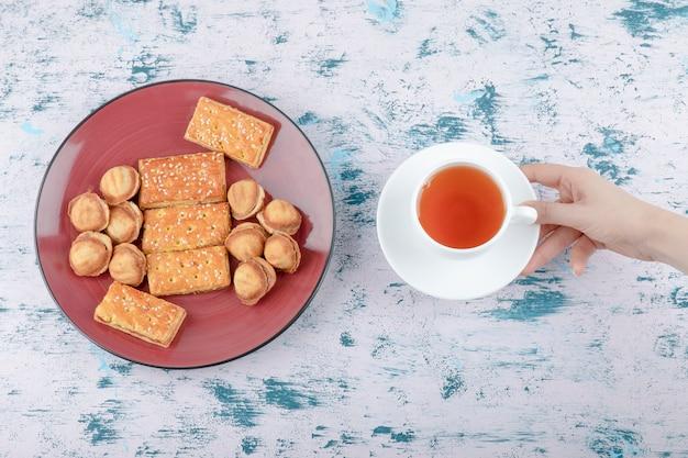 Weibliche hand, die eine tasse tee mit shortbread-nüssen mit kondensmilch hält.