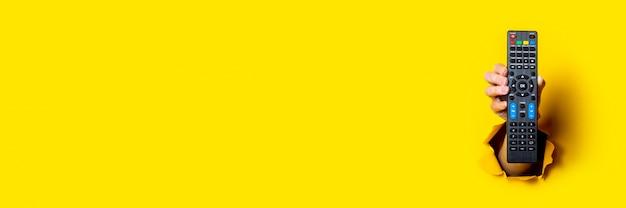 Weibliche hand, die eine tv-fernbedienung auf einem hellen gelben hintergrund hält
