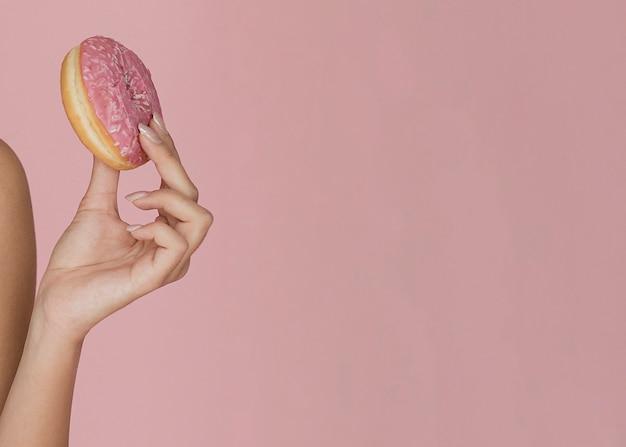 Weibliche hand, die einen appetitanregenden krapfen anhält