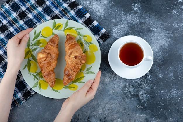 Weibliche hand, die einen bunten teller mit frisch gebackenen croissants nahe einer tasse tee hält