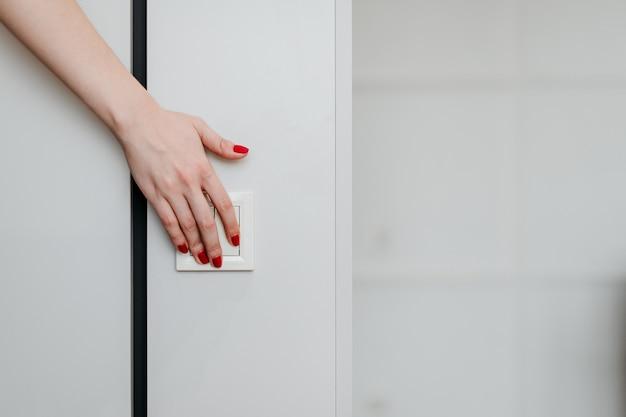 Weibliche hand, die einen elektrischen lichtschalter an der wand dreht