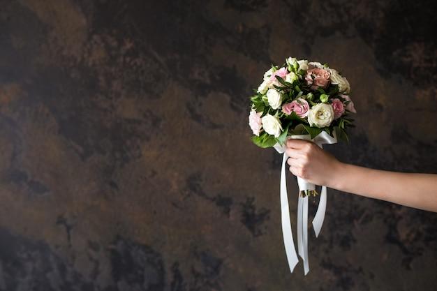 Weibliche hand, die einen hochzeitsblumenstrauß auf dunkelheit hält
