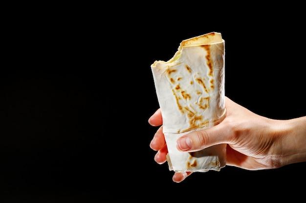 Weibliche hand, die einen kebab auf einem schwarzen hintergrund hält