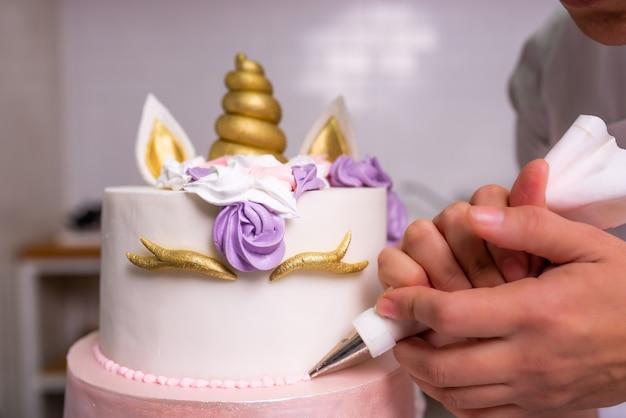 Weibliche hand, die einen kuchen für geburtstagsfeier, bäckerliebhaber, lebensmittelstylingschule, cheffs verziert