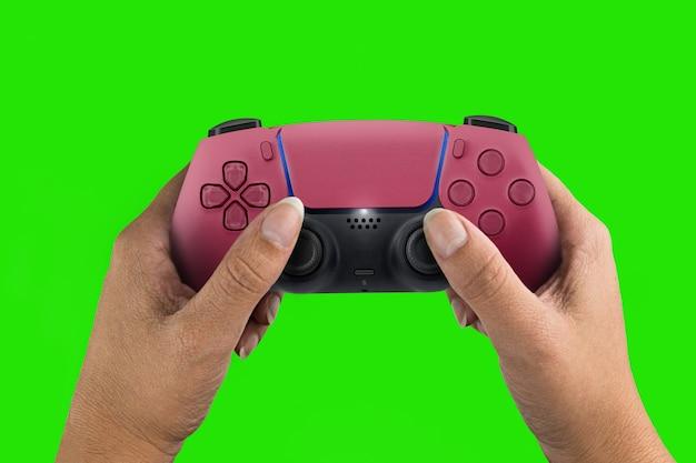 Weibliche hand, die einen roten gamecontroller der nächsten generation hält, der auf grünem bildschirmhintergrund lokalisiert wird. chroma-key.