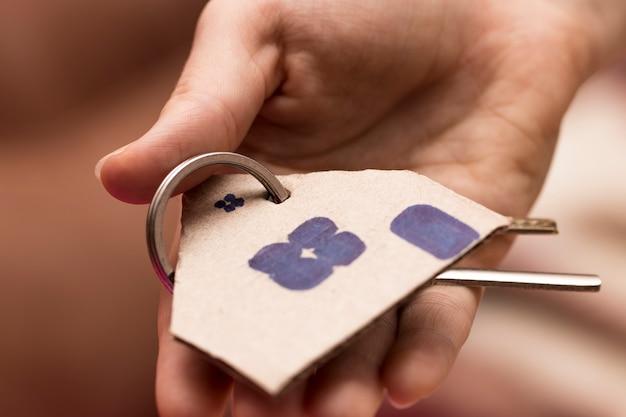 Weibliche hand, die einen schlüssel zum haus darstellt, der immobilienmakler.