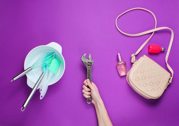 Weibliche hand, die einen schraubenschlüssel auf dem hintergrund der schüssel mit küchenwerkzeugen, taschen und flasche parfüm hält