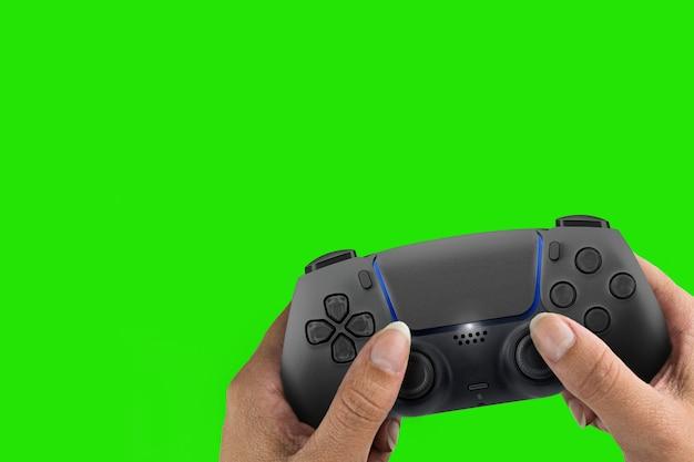 Weibliche hand, die einen schwarzen gamecontroller der nächsten generation hält, der auf grünem bildschirmhintergrund lokalisiert wird. chroma-key.