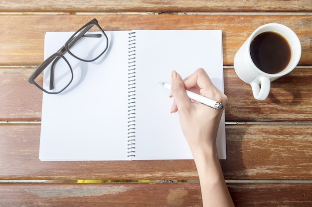 Weibliche hand, die einen stift hält. tabelle mit notizblöcken. tasse kaffeepause. schwarzes glas.